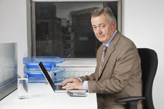 Portrait of middle-aged businessman using laptop at desk in office Royalty Free Stock Image
