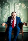 Mad bussinesman shouting. Portrait of middle aged caucasian bussinesman wearing blue suit and red tie sitting in a chair and shouting straight in camera Royalty Free Stock Photo