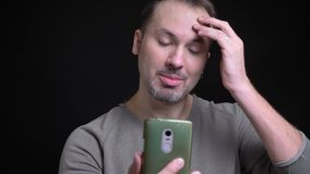 Portrait of middle-aged concentrated caucasian man with earring talking joyfully in videochat on smartphone on black. Background stock footage