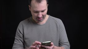 Portrait of middle-aged concentrated caucasian man with earring watching joyfully into smartphone on black background. Portrait of middle-aged concentrated stock footage