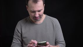 Portrait of middle-aged concentrated caucasian man with earring watching seriously into smartphone on black background. Portrait of middle-aged concentrated stock footage