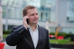 Middle aged confident businessman, talking on the phone, outside. Portrait of middle aged confident businessman at the office, outside. Smiling Stock Photos
