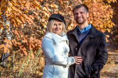 Portrait of Middle Aged couple in Autumnal Park. Husband and Wife Embracing Staying on Forest Alley with Bright Fall Colors Leaves Background Stock Photo