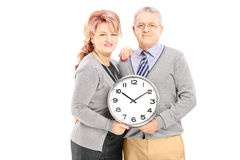 Portrait of middle aged couple holding wall clock Stock Image