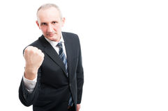 Portrait of middle aged elegant man showing fist. Wearing suit and tie isolated on white background with copy text space Stock Images