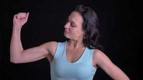 Portrait of middle-aged female bodybuilder demonstrating her biceps into camera on black background. Portrait of middle-aged female bodybuilder demonstrating stock video footage