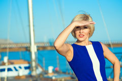Portrait of middle-aged gorgeous blond woman in blue dress looking into the distance with her hand over her eyes. Stock Photos
