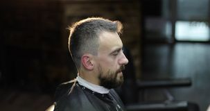 Portrait of the middle aged man in backlight at a barbershop. The hairdresser with tattoos on his hands dries client`s hair with a hairdryer and cuts hair stock footage
