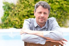 Portrait of middle aged man caucasian smiling and looking at camera outside at home house garden pool background. A Portrait of middle aged man caucasian smiling royalty free stock photos