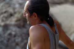 Portrait middle aged man with long hair sideview, outside and rock on background Royalty Free Stock Photos