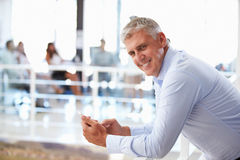 Portrait of middle aged man in office using smart phone,phone Stock Photo