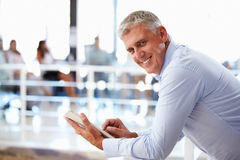 Portrait of middle aged man in office using tablet Stock Photo