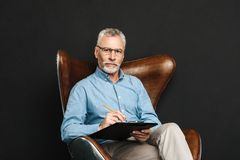 Portrait of middle aged man 60s with grey hair and beard sitting. On wooden armchair and holding clipboard with documents isolated over black background Royalty Free Stock Photo