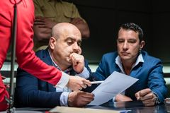 Middle-aged man calling his attorney during a difficult police interrogation. Portrait of a middle-aged men calling his attorney in order to ask for legal stock image