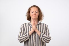 Portrait of middle aged pretty european female, holding hands in pray with closed eyes royalty free stock image