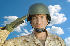 Portrait of middle-aged soldier in military uniform saluting against cloudy sky Stock Image