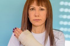 Woman with broken arm bone in cast, plastered hand on blue background. royalty free stock photography