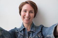 Portrait of a middle-aged woman in a denim jacket. She hugs someone or makes a selfie Stock Image