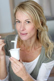 Portrait of middle aged woman eating yoghurt Royalty Free Stock Photos