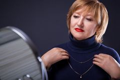 Portrait of a middle-aged woman trying on a golden necklace. Looking in the mirror on black background Royalty Free Stock Photos