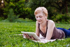 Portrait of middle aged woman using tablet in the park royalty free stock images