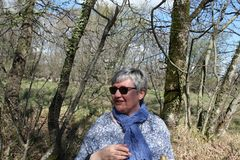 Portrait of a middle-aged woman through the walk in nature in a good mood. Portrait of a middle-aged woman through the walk in nature with sunglasses and smile Stock Image