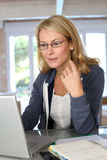 Portrait of middle-aged woman working on laptop Royalty Free Stock Photos