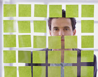 Portrait of a middle eastern business man behind sticky notes in bright glass office. Serious executive business man brainstorming using green adhesive notes in Royalty Free Stock Photos
