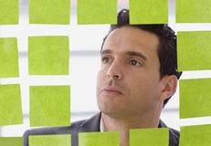 Portrait of a middle eastern business man behind sticky notes in bright glass office. Serious executive business man brainstorming using green adhesive notes in Royalty Free Stock Photography