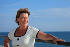 Portrait of middleaged woman on balcony over sea Stock Photography