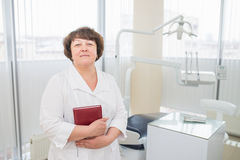 Portrait of midle aged female dentist ,standing in her dentist office and holding a book or diary. Stock Photos
