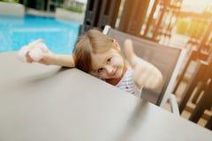 Portrait mignon de peu de fille d'enfant montrant des pouces vers le haut ou comme sur de piscine Photos stock