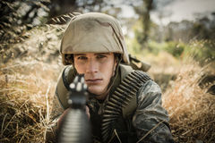 Portrait of military soldier aiming with a rifle. In boot camp stock image
