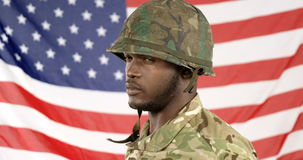 Portrait of military soldier wearing helmet. Against the US flag background 4k stock video footage