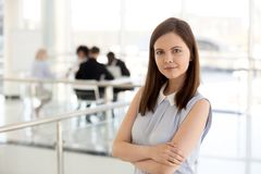 Portrait of millennial female employee posing with arms crossed. Portrait of smiling millennial female employee posing with arms crossed standing in office royalty free stock photos