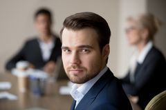 Portrait of millennial male employee making picture at meeting. Portrait of confident male employee looking at camera making professional photo during briefing stock photography