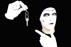 Portrait of the mime in white gloves with a key. On a black background Stock Image