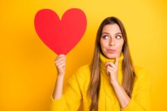 Portrait of minded girl get red big paper card heart from secret admirer think thoughts who he is wear knitted collar