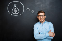 Portrait of minded man crossed hands over blackboard. money conc. Portrait of minded, suited man standing crossed hands over blackboard. money concept stock image