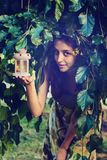 Portrait of mischievous fairy. Who peeps out of green foliage, holding the lantern with a burning candle in her hands. Magic scene in nature. Toned image Royalty Free Stock Images