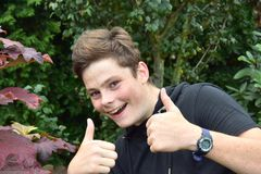 Portrait of a mischievously grinning teenage boy. Portrait of a happy mischievously grinning teenage boy with many freckles, thumbs up royalty free stock image