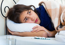 Portrait of miserable girl wth flu at home. Sad teenage girl with high fever and flu in bed royalty free stock images