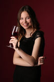 Portrait of miss in black dress with wine. Close up. Dark red background Royalty Free Stock Photo
