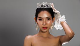 Miss Pageant Beauty Contest in white gray sequin. Portrait of Miss Pageant Beauty Contest in white gray sequin Evening Ball Gown dress sparkle light Silver royalty free stock photo