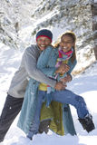 Portrait of mixed race couple hugging in snow Stock Images