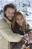 Portrait of mixed race couple hugging in snow Stock Photo