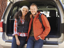 Portrait of mixed race couple sitting in open back of a car Stock Photo