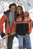 Portrait of mixed race couple with snow sled Royalty Free Stock Photo