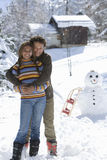 Portrait of mixed race couple standing in snow with snowman Royalty Free Stock Photos