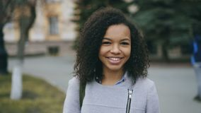 Portrait of mixed race curly student girl smiling into camera and laughing at city street. Portrait of mixed race curly student woman smiling into camera and stock video